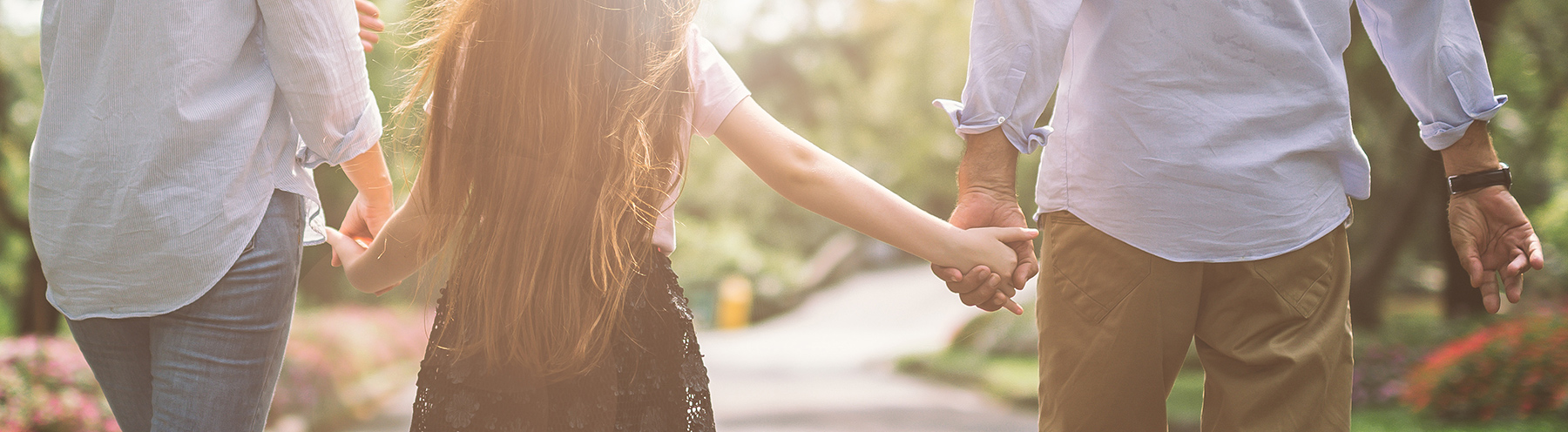 Parents hold hands with daughter